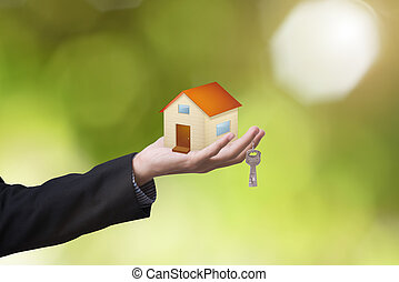 business salesman hand holding home and home key concept...