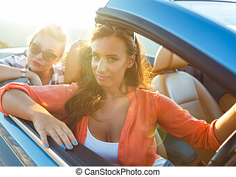 Two young girls driving a cabriolet