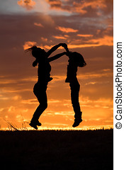 Mother and daughter leap at sunset. - A mother and daughter...