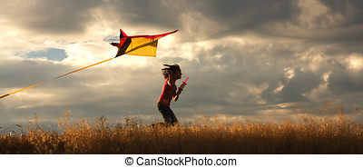 Girl flying a kite. - A panorama of a girl happily flying...