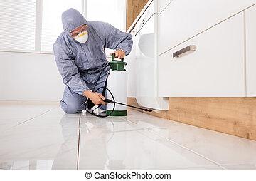 Exterminator Spraying Pesticide In Kitchen