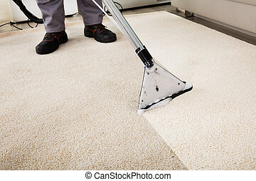 Person Cleaning Carpet With Vacuum Cleaner - Close-up Of A...