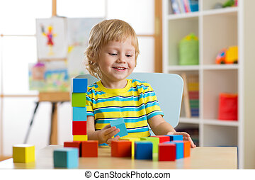 kid boy playing with block toys in day care center