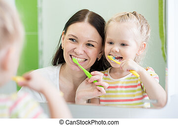 Mother And Child Daughter Brushing Teeth Together - Mother...