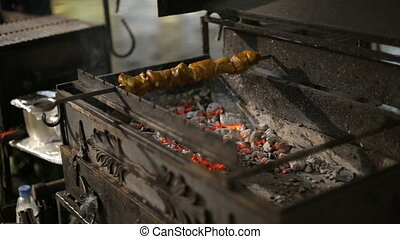 A barbecue skewer spinning on the grill. Fresh steaming meat...