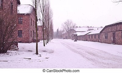 Auschwitz Birkenau, German Nazi concentration and extermination camp. Barracks in falling snow