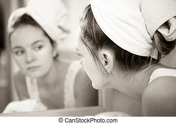 Woman washing face in bathroom. Hygiene - Woman cleaning...