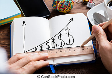 Person Hand Drawing Dollar Growth Chart On Notebook