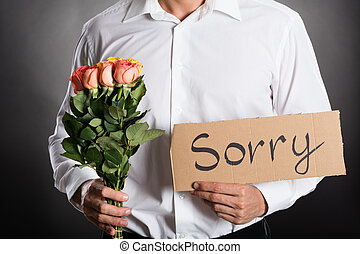 Man Holding Roses And Text Sorry Written On Cardboard...
