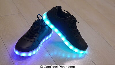 Black child shoes with blinking led sole on the wooden...