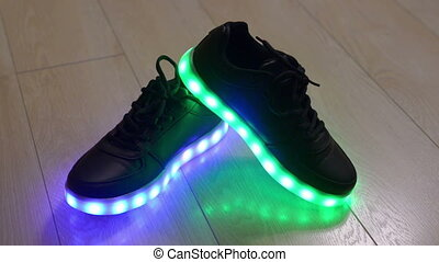 Black child shoes with blinking led sole on the wooden floor