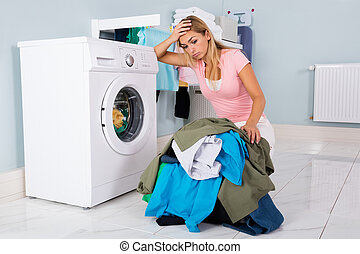 Unhappy Woman Looking At Clothes In Utility Room - Unhappy...