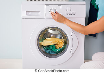Person Hand Pressing Button Of Washing Machine - Close-up Of...