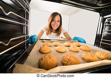 Happy Woman Baking Cookies In Oven