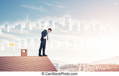 Businessman looking down from roof and modern cityscape at backg