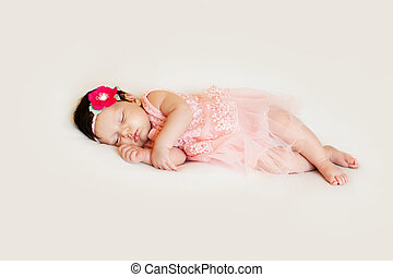 little girl in dress sleeping on white blanket