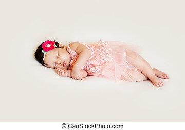 little girl in dress sleeping on white blanket