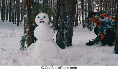Man in the pine Forest Sculpts Snowman. Snowman in a Pine...