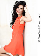 Brunette woman wearing orange short dress in urban...