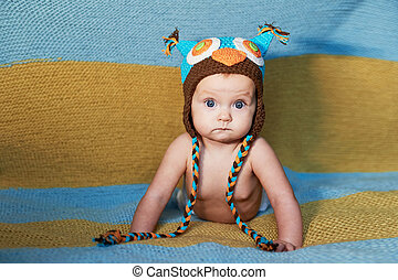 Little newborn baby with big eyes hat-knitting on a plain...