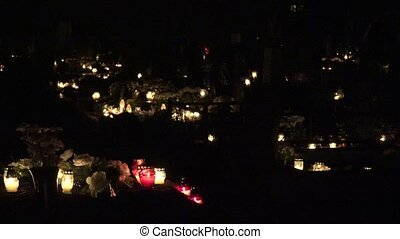 Family members visit graveyard at dark night and candle...
