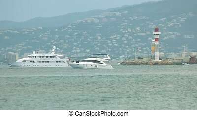 Motor yacht near lighthouse. Town on the hill. Travel to...