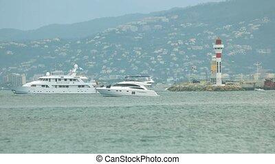 Motor yacht near lighthouse.
