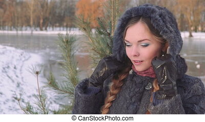 Young beautiful woman posing over winter forest. Outdoor winter portrait over snowy background. slow motion from 50 fps Full HD
