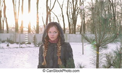 Young beautiful woman posing over winter forest. Outdoor winter portrait over snowy background. slow motion from 50 fps