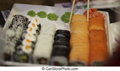 Hand with chopsticks taking sushi. Sushi rolls on white...