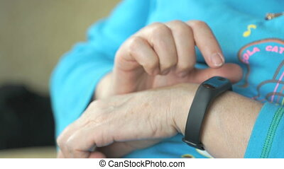 Woman looks at the wristband fitness tracker - Black...