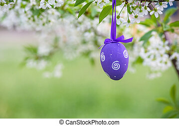 Several Easter colored eggs hanging on a tree branch color...