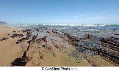 Small rocks formations on sandy beach. - Atlantic sandy...