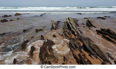 Small rocks formations on sandy beach. - Small rocks...