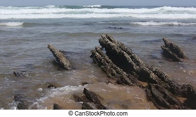 Small rocks formations on sandy beach. - Small rocks...