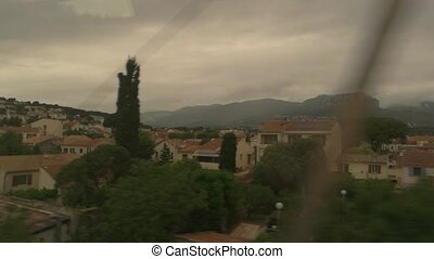 Landscape in train window. Town buildings and mountains....