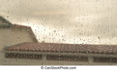 Water drops on train window. Blurred rooftop and sky.