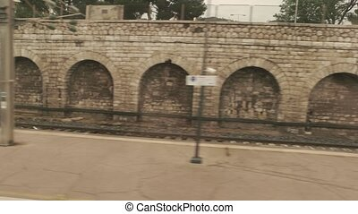 Platform in train window. Old stone wall and railway. Catch...