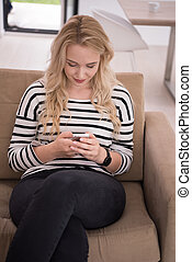 woman sitting on sofa with mobile phone - young happy woman...