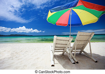 Two beach chairs and colorful umbrella on perfect tropical...