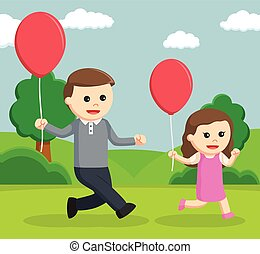 dad and daughter walking with balloon in the park