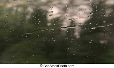 Droplets moving on train window. Blurred green trees....