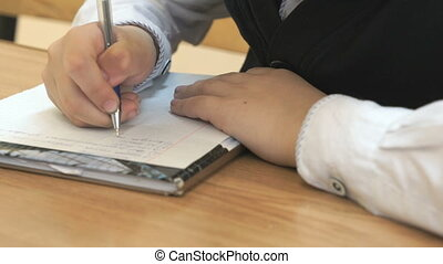 Schoolboy writes the text in the notebook indoors -...