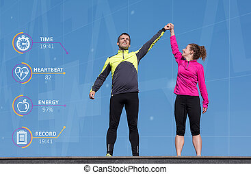 Happy fitness runner couple with arms raised up in winning...