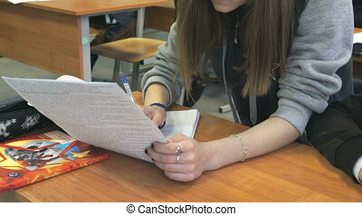 Schoolgirl sitting at a school desk on the lesson - The...