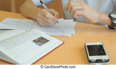 Student writes the text in a copybook on a lesson - Student...