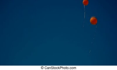 Two orange baloons flying up in the blue sky copyspace