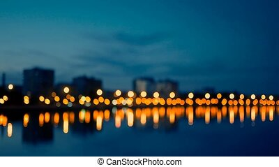 Waterfront area of city in night time, defocused shot of...