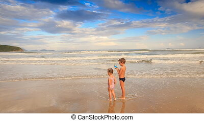Kids Small Girl with Pigtail Boy Stand in Shallow Waves on Beach