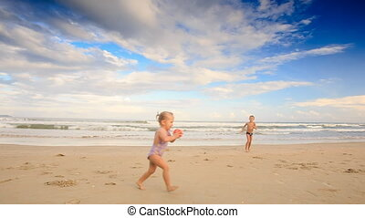 Small Pigtail Girl Runs with Ball Boy Stands on Sand Beach -...